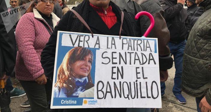 Una mujer sostiene un cartel en apoyo a Cristina Fernández durante el juicio oral en su contra