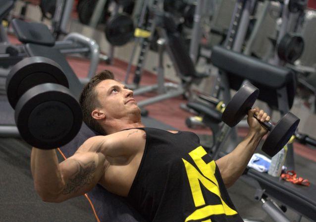 Un hombre con pesas en un gimnasio