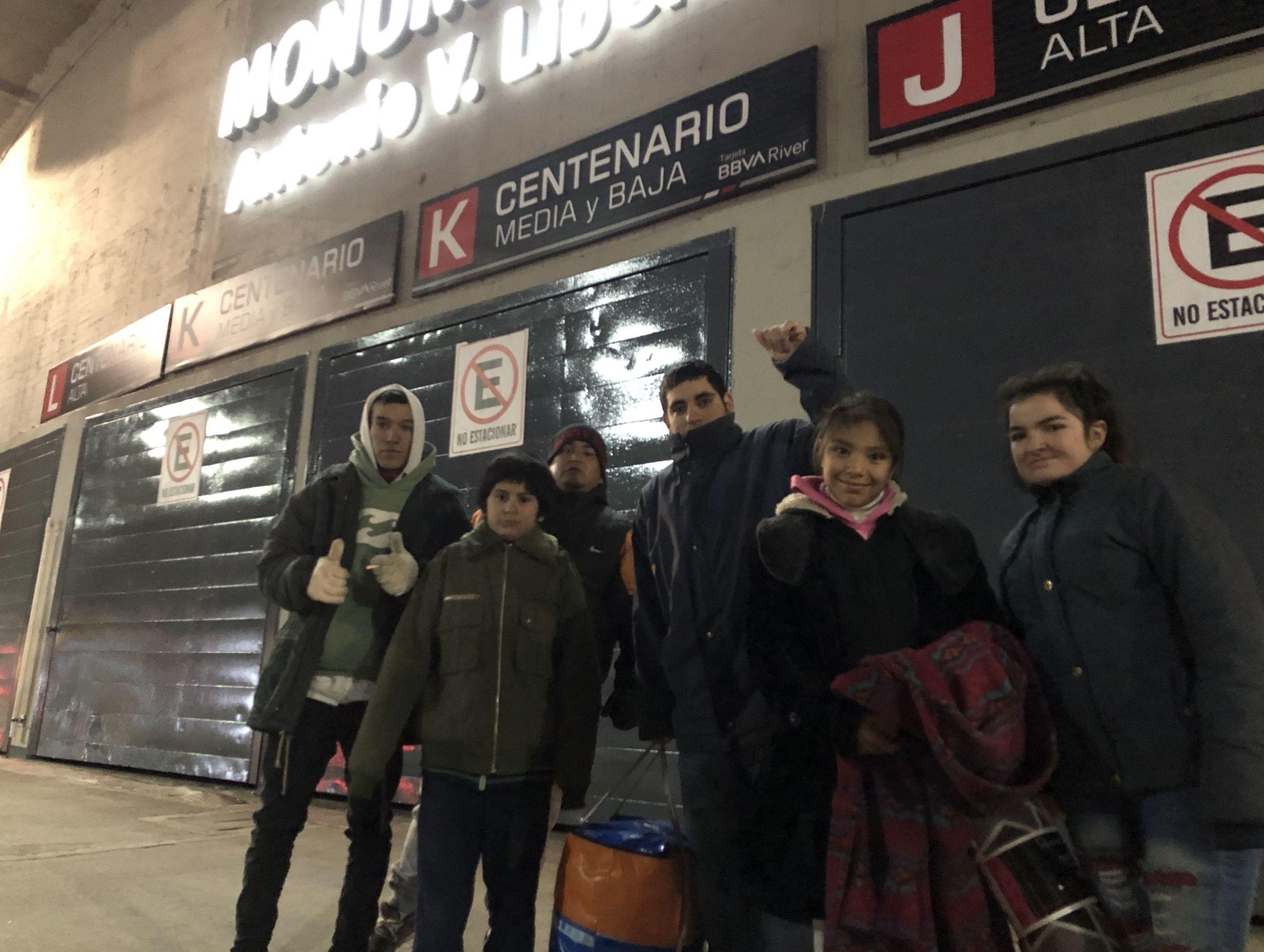Una familia espera donaciones en las afueras del Estadio Monumental del River Plate en Buenos Aires