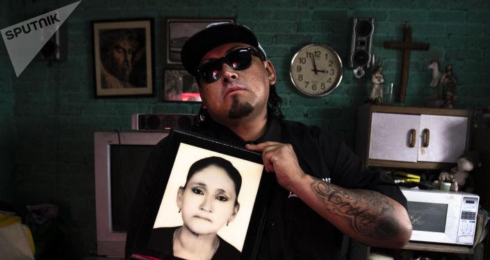 Gonzalo posa para foto con el retrato de su madre