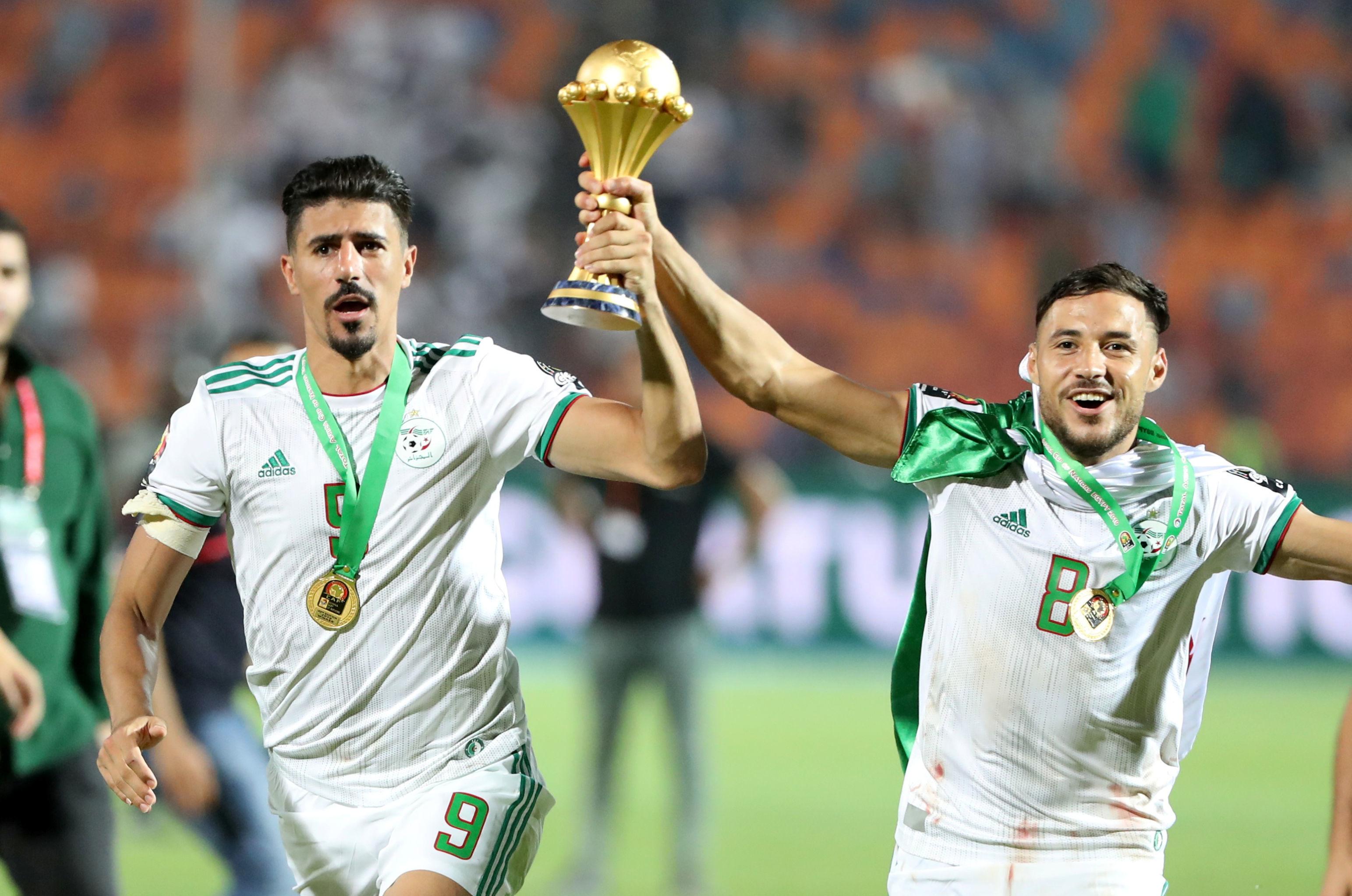 Los futbolistas argelinos Baghdad Bounedjah (izda.) y Youcef Belaili (dcha.) celebran su victoria en la Copa Africana de Naciones de 2019, en el Cairo (Egipto), el 19 de julio de 2019