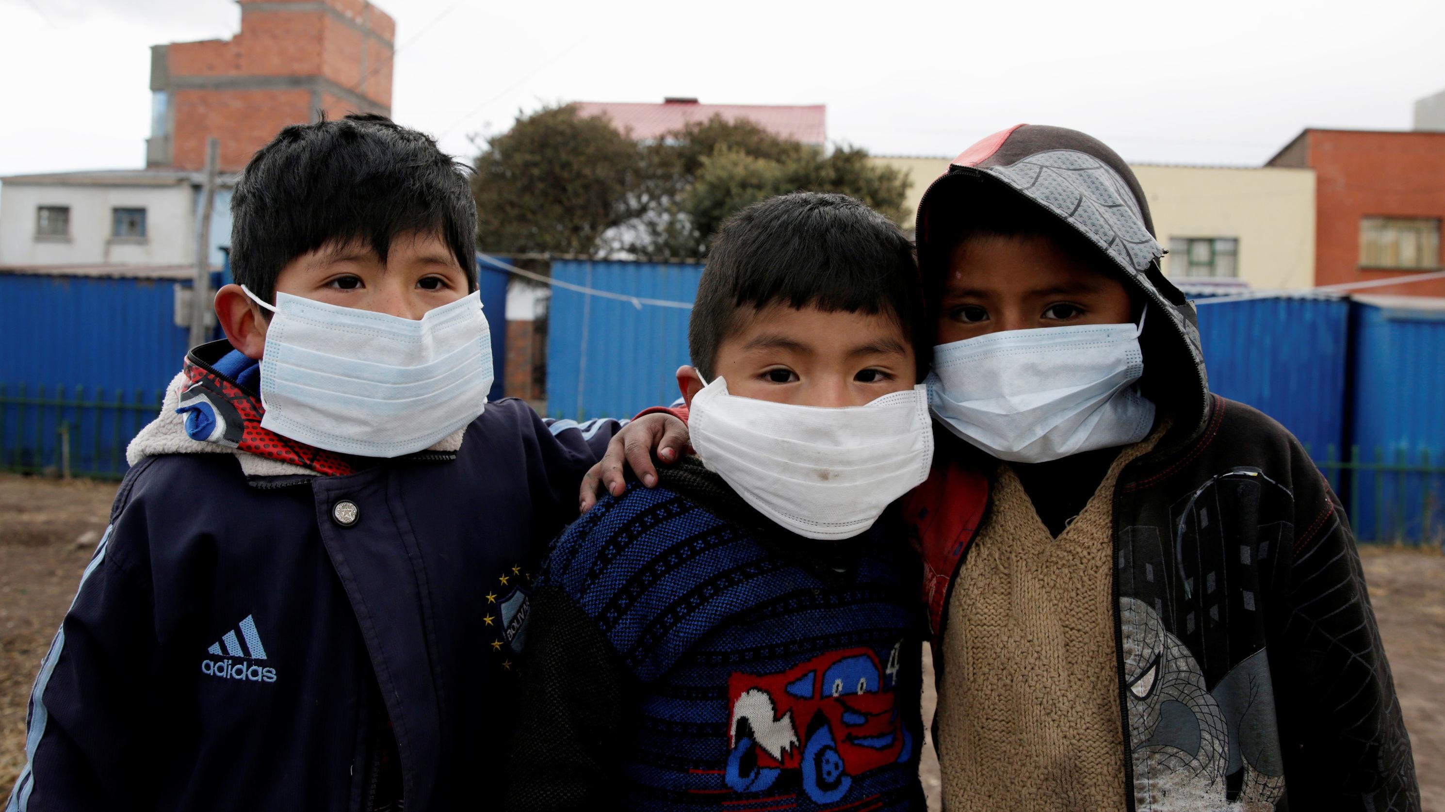 Niños de Santiago de Machaca (Bolivia) usan máscaras para protegerse de las cenizas del volcán Ubinas, el 21 de julio de 2019