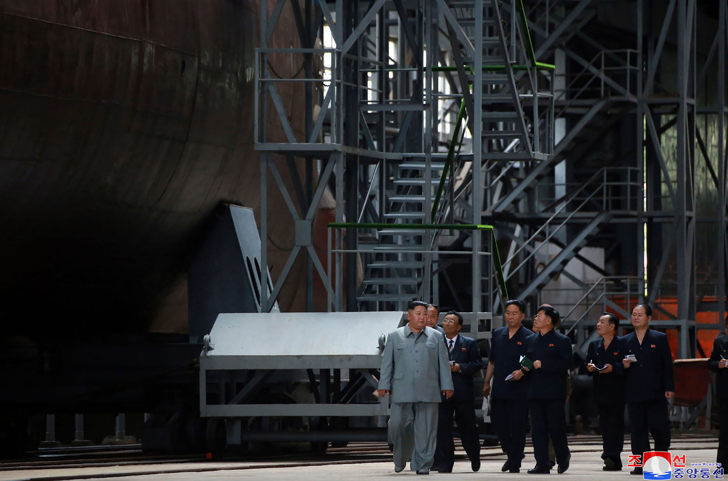 El líder norcoreano, Kim Jong-un, acompañado de varios oficiales y técnicos junto al submarino.