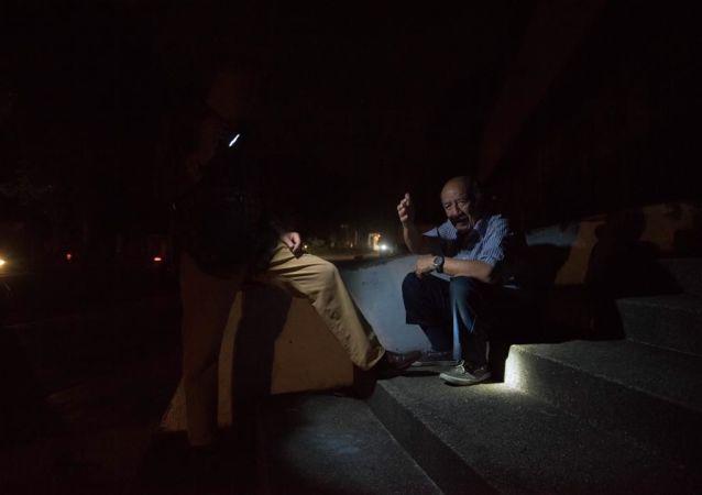 Dos hombres durante el nuevo apagón en Venezuela