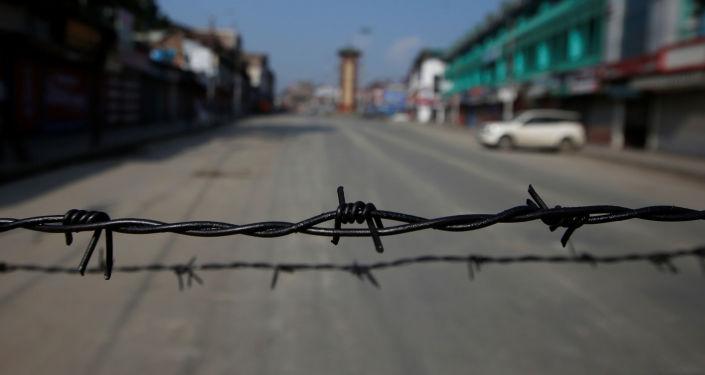 Alambre de púas en una carretera desierta durante las restricciones en Srinagar, Cachemira