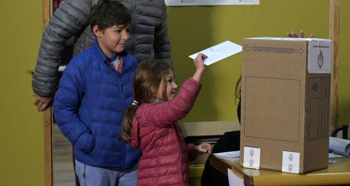 Una niña depositando el voto de su padre