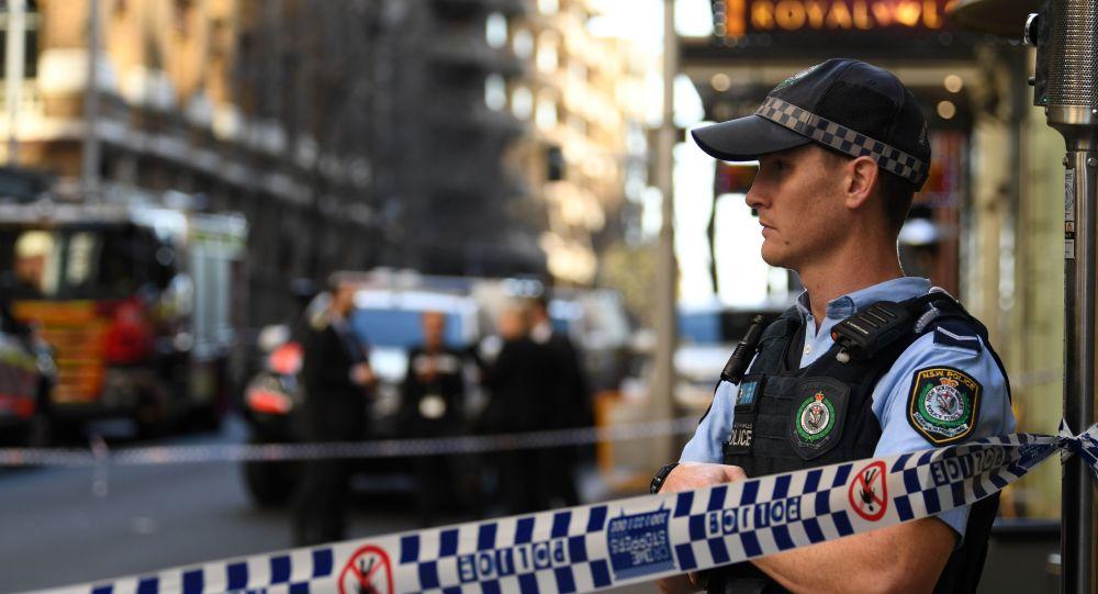 Un policía junto a la escena de crimen después de que un hombre apuñalara a una mujer e intentó apuñalar a otros en el centro de Sídney