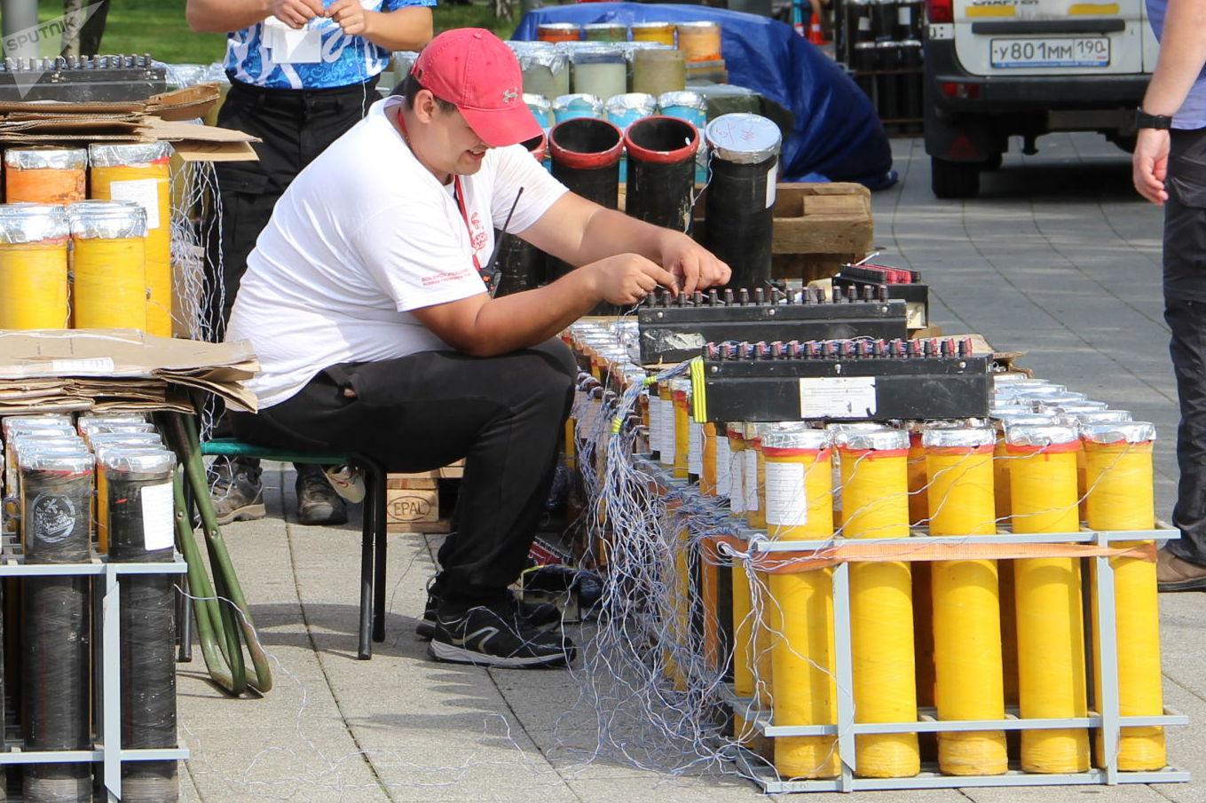 Un pirotécnico conecta los cables de disparo a los fuegos artificiales