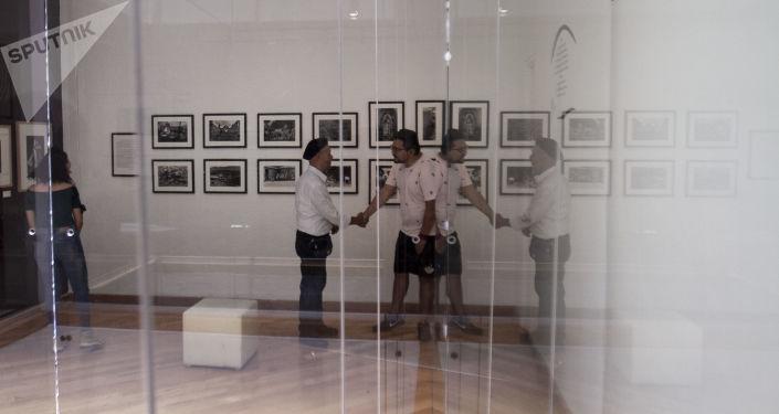 Rubén Pax saluda a una persona que visitó su exposición en el Museo de la Fotografía de la ciudad de México