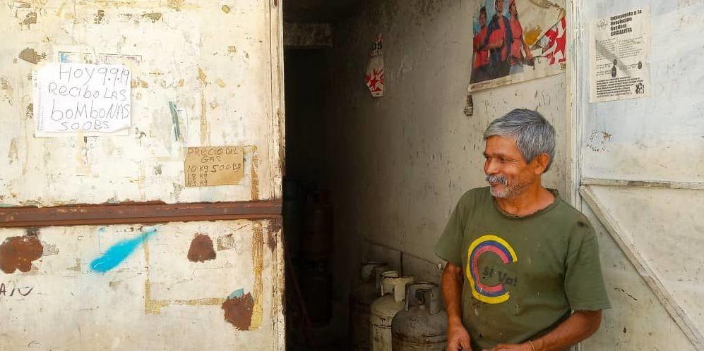 Vocero encargado de un concejo comunal en la puerta de del depósito de bombonas donde se lee el cartel con el monto del aporte que hacen los vecinos, Caracas, Venezuela