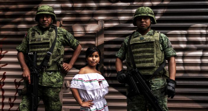 Elementos de las fuerzas armadas posan con una niña durante el desfile militar en la ciudad de México