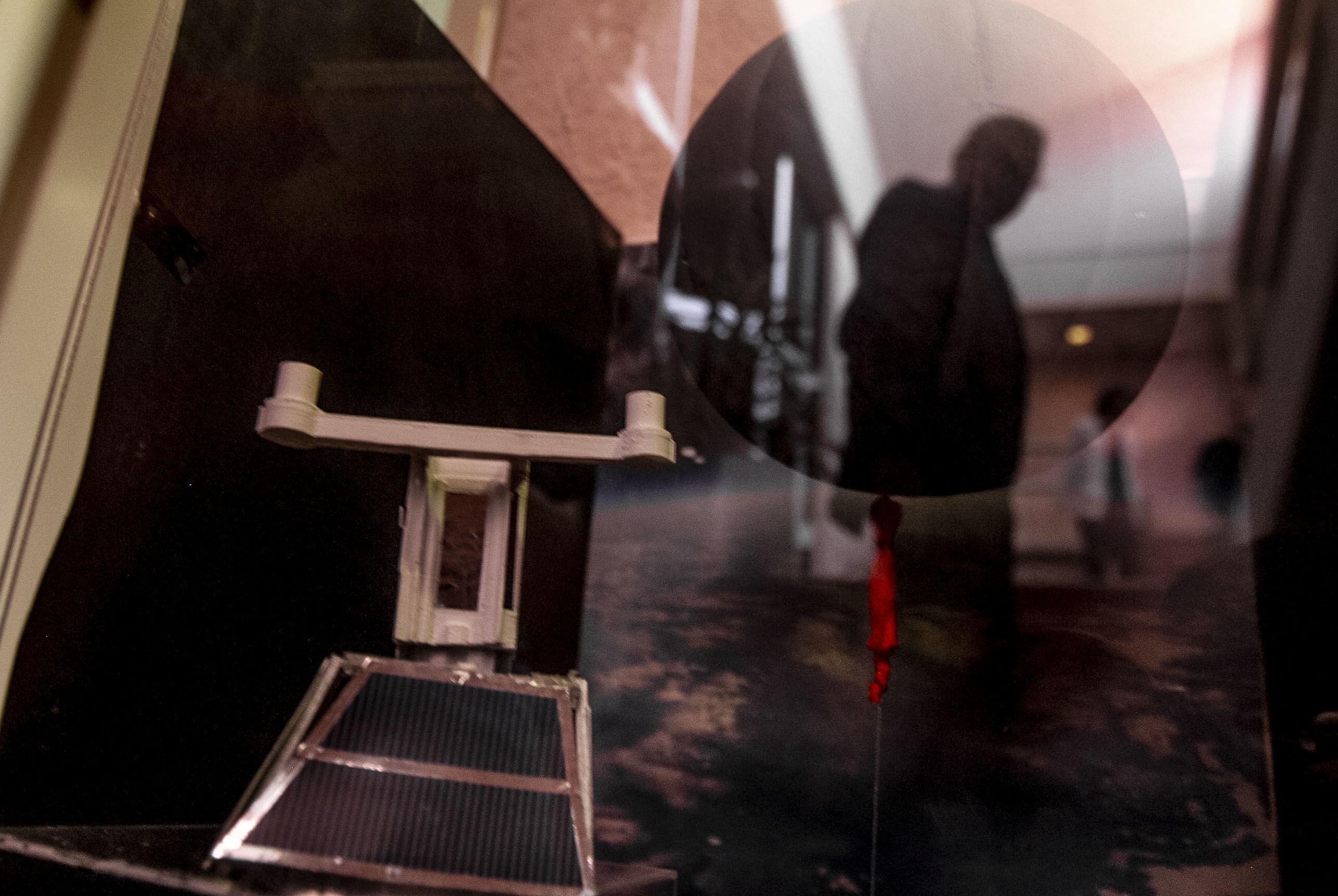 Gustavo Medina, investigador del Instituto de Ciencias Nucleares de la UNAM se refleja frente a una maqueta del EUSO-SPB un telescopio UV para la detección de rayos cósmicos de ultra-alta energía lanzado en abril de 2017 en un globo de súper-presión