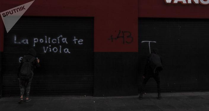Asistentes a la manifestación a cinco años de la desaparición forzada de los 43 estudiantes de Ayotzinapa grafitean a su paso.
