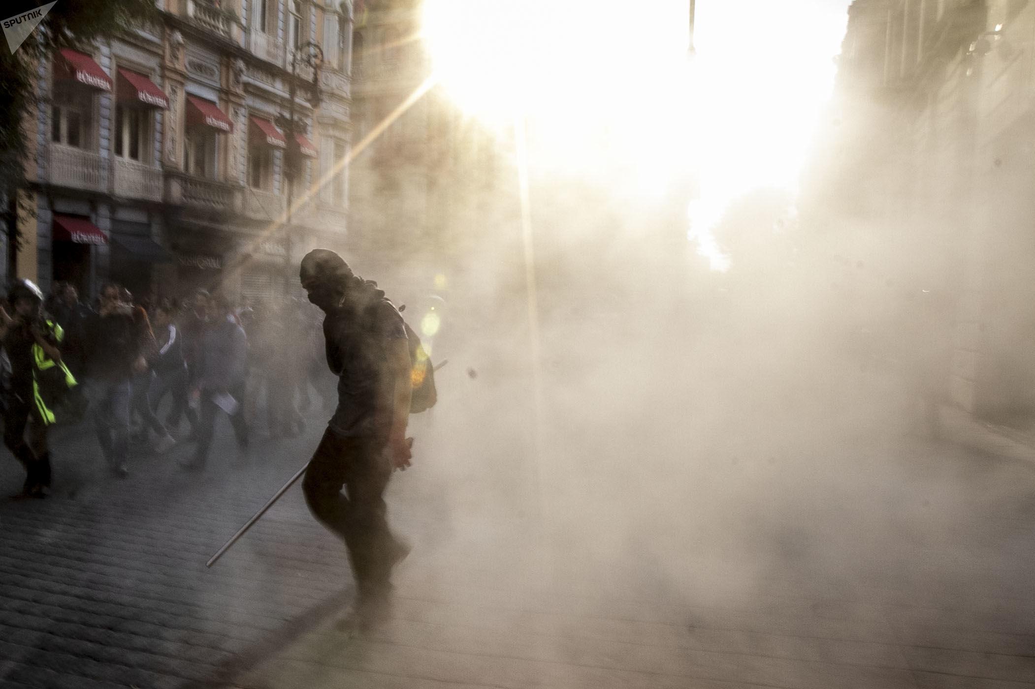 Manifestante rodeado de humo de un extintor en protesta por los cinco años de la desaparición forzada de 43 estudiantes de magisterio en el sur de México.