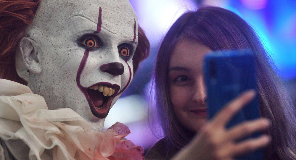 Una visitante de Comic Con se hace un selfí con un 'cosplayer' del payaso Pennywise