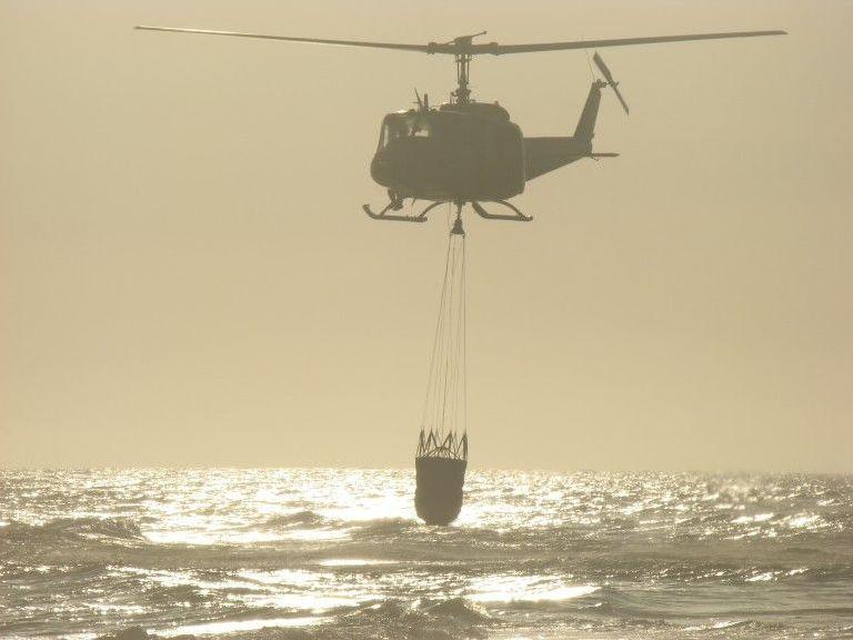 El Bell UH-1H Huey de la Fuerza Aérea Uruguaya, trabajando con un helibalde
