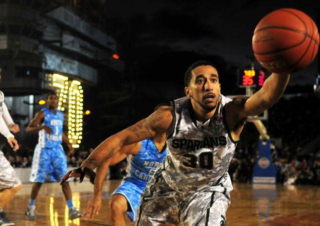 Un jugador de baloncesto trata de hacerse con la pelota