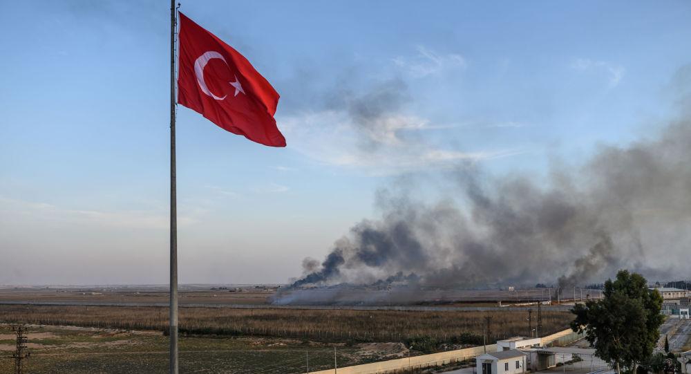 La bandera de Turquía y el humo tras los ataques aéreos en Siria