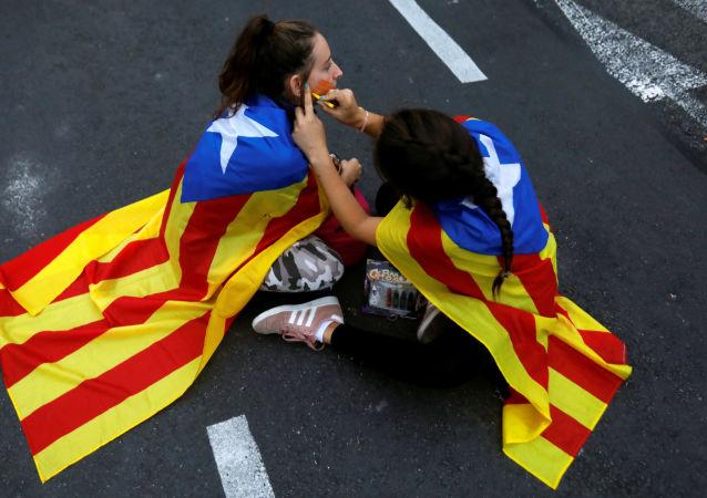 Los manifestantes con la bandera independista de Cataluña se alistan para las protestas