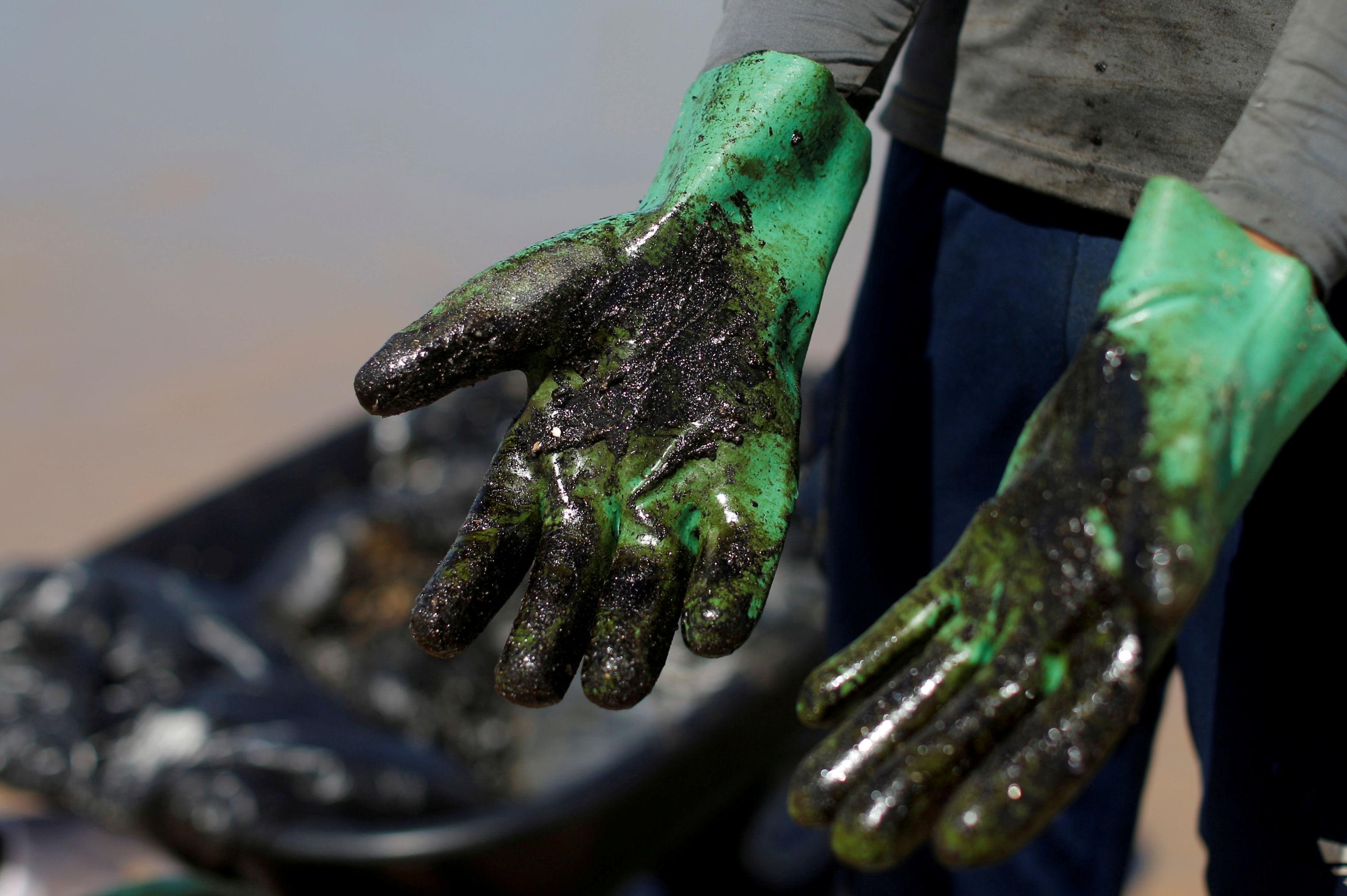 Las manos después de limpiar la playa del petróleo