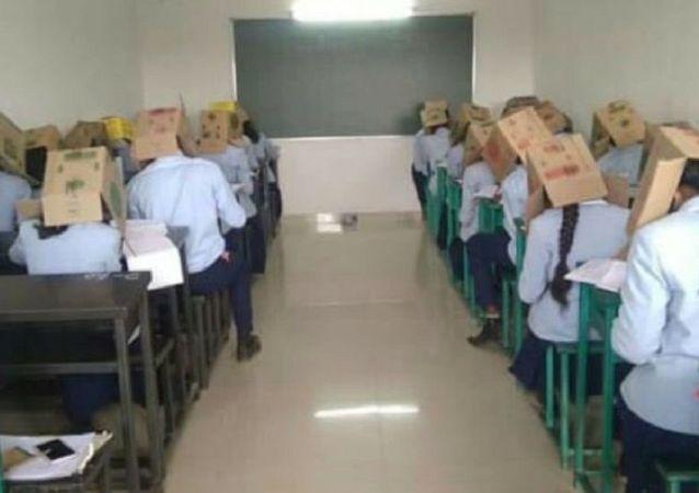 Una escuela hace a sus alumnos usar cajas en la cabeza en los exámenes