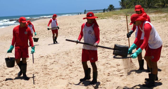 Trabajadores municipales limpiando de petróleo la playa de Mata de Sao Joao, Brasil