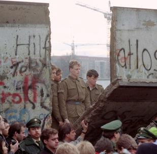 Guardias fronterizos de Alemania Oriental aparecen tras el muro de Berlín después que los manifestantes derribaron un segmento