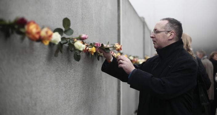 Un hombre coloca una flor en una grieta del antiguo Muro de Berlín para conmemorar a las víctimas del muro en 2014