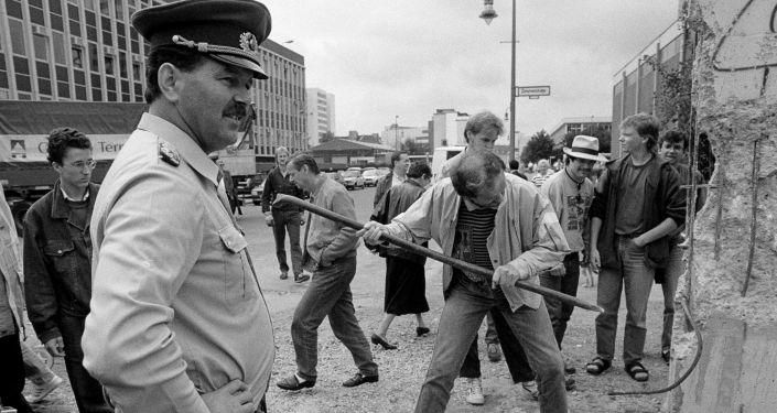 Policía fronterizo de Alemania Oriental observa a un hombre martillando una sección del Muro de Berlín en 1989