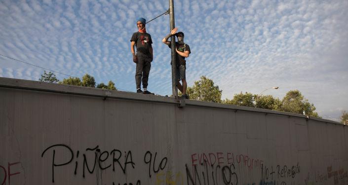 Manifestantes chilenos contra el Gobierno de Chile parados sobre un muro en Santiago