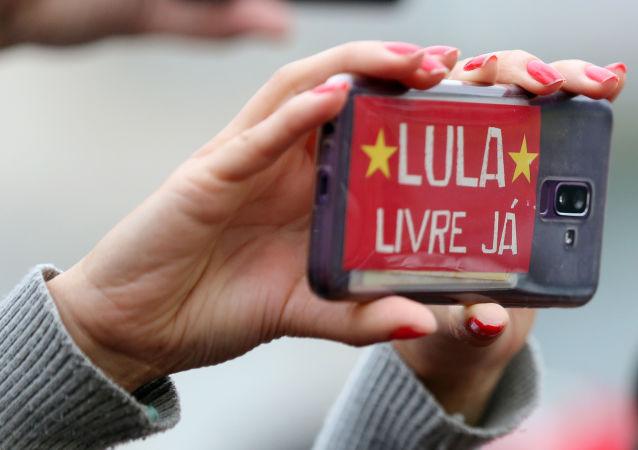 Una mujer sostiene un teléfono celular con un mensaje en apoyo a Lula