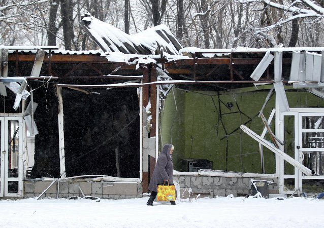 A woman walks on the snow near destroyed shops in Kievsky district in Donetsk, eastern Ukraine, November 30, 2014
