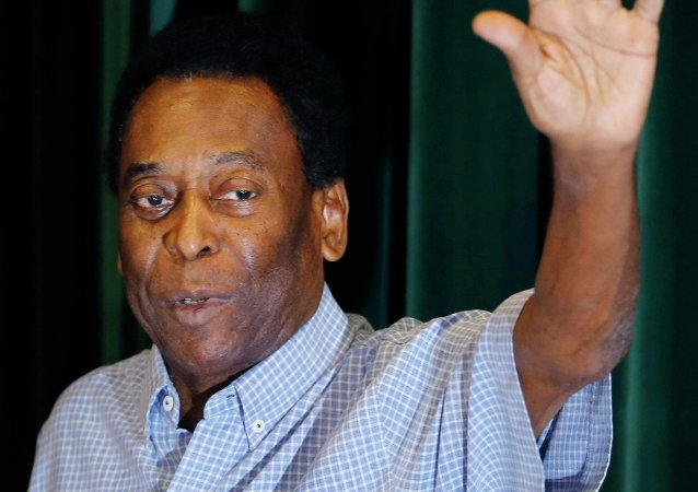 Brazilian soccer legend Pele waves as he leaves a news conference in Sao Paulo, December 9, 2014.