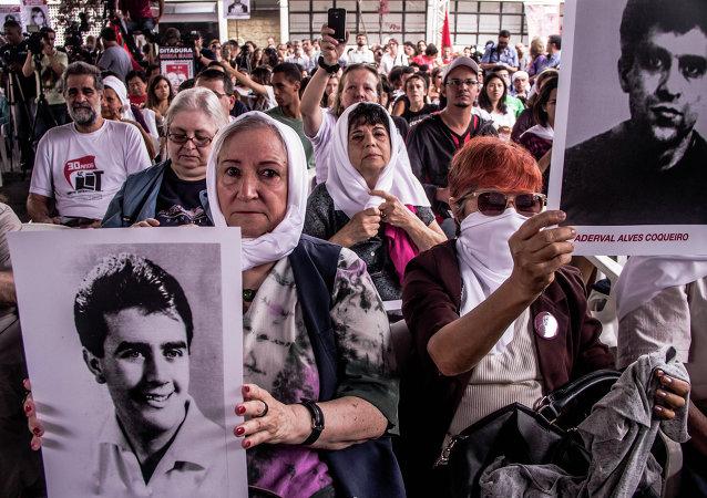 Gente con las fotos de los desaparecidos durante la dictadura militar en Brasil