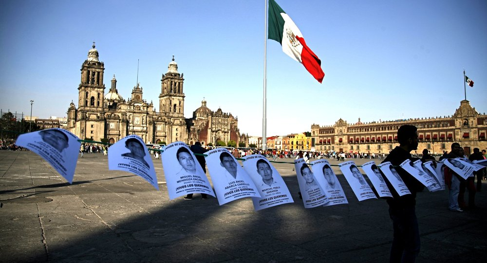 Leaflets with the images of 43 missing students from the state of Guerrero, are shown before a massive protest march, at the Zocalo in Mexico City