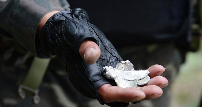 Ополченец показывает осколки разорвавшегося снаряда в здании обладминистрации в Луганске