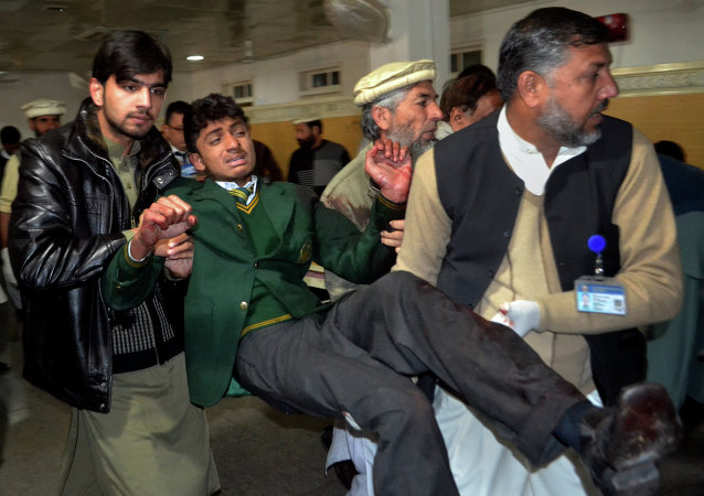 Pakistani volunteers carry a student injured in the shootout at a school under attack by Taliban gunmen, at a local hospital in Peshawar, Pakistan,Tuesday, Dec. 16, 2014