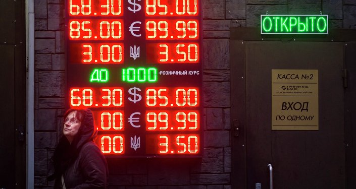 People wait to exchange currency near a sign advertising currency exchange rates at an exchange office in Moscow, Russia, Tuesday, Dec. 16, 2014