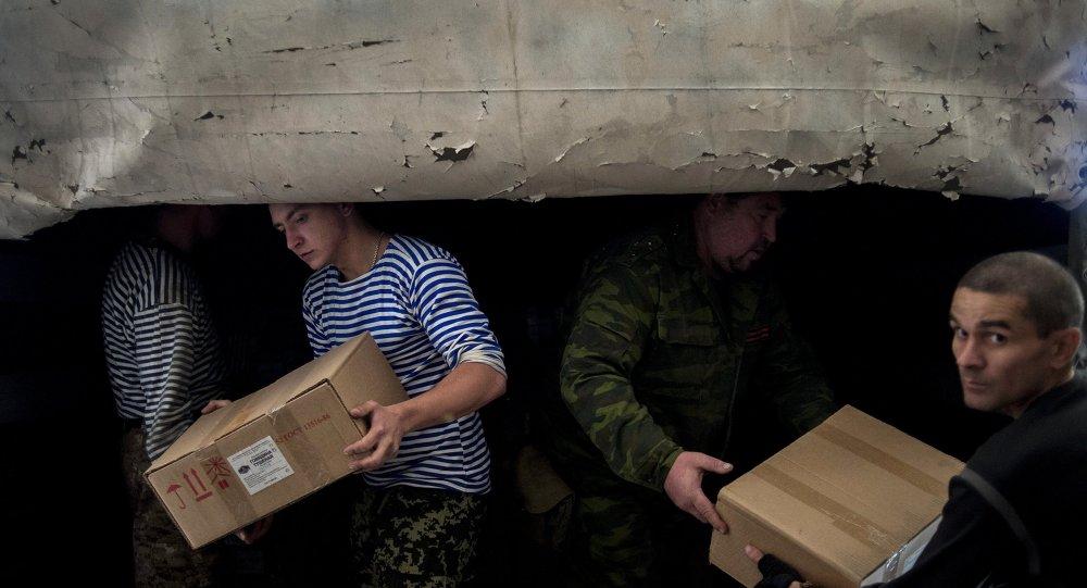 Мужчины разгружают один из грузовиков третьей гуманитарной колонны