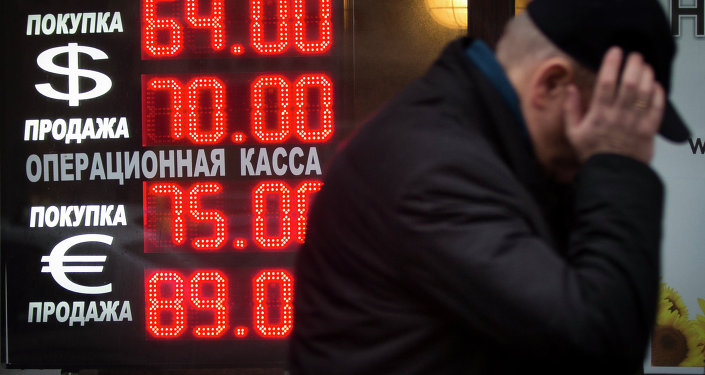 A man walks by a sign advertising currencies of an exchange office in Moscow, Russia