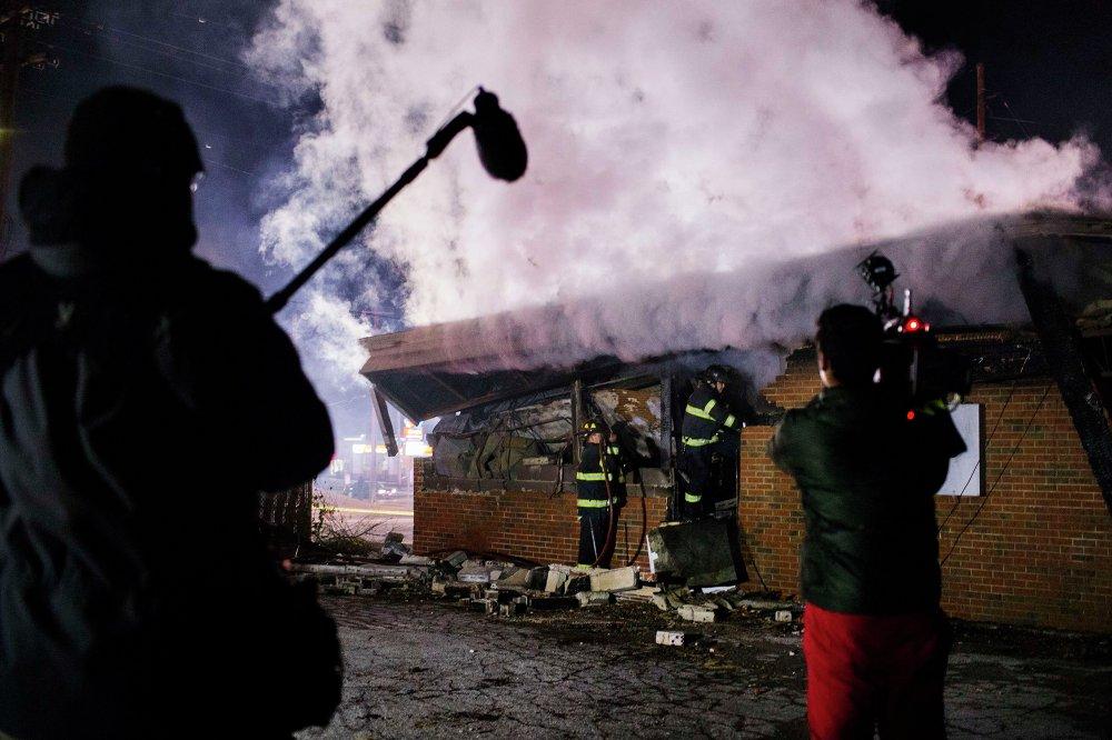 Телеоператор снимает тушение пожара в здании, загоревшемся в результате беспорядков в Фергюсоне