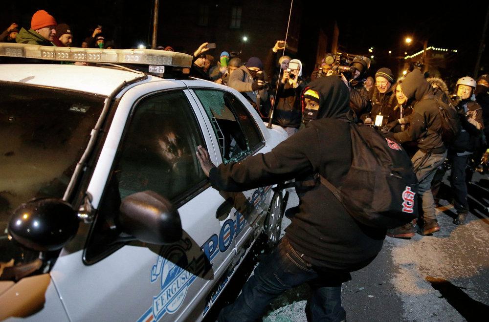 Протестующие разбивают полицейский автомобиль на улице города Фергюсон, США