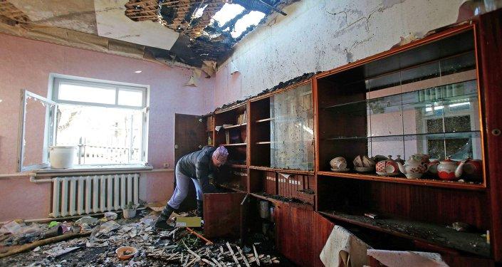 Женщина убирается в доме, поврежденном в результате обстрела в Донецке
