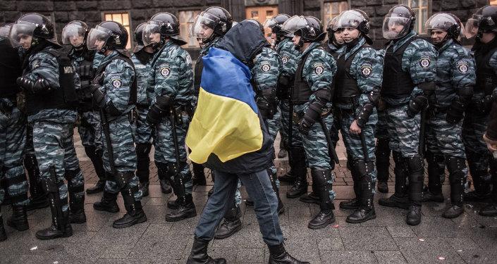 Сторонник евроинтеграции Украины и сотрудники милиции у здания правительства страны в Киеве