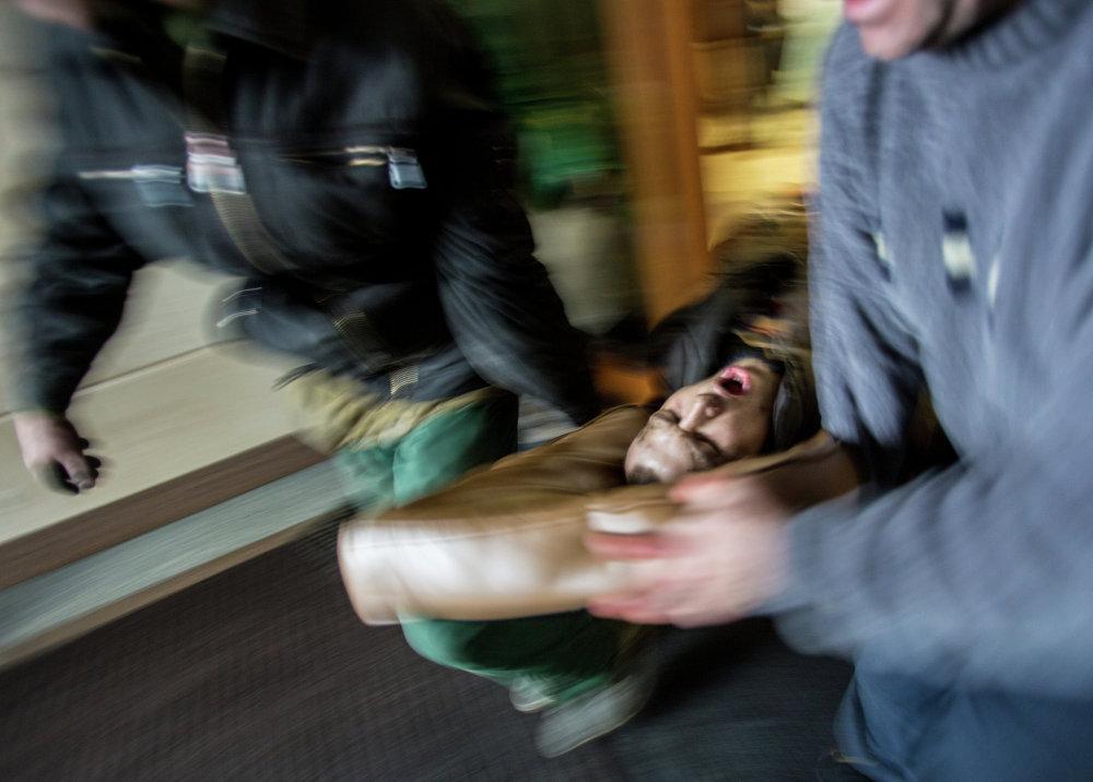 Сторонники оппозиции несут раненного во время столкновений с сотрудниками правопорядка на площади Независимости в Киеве