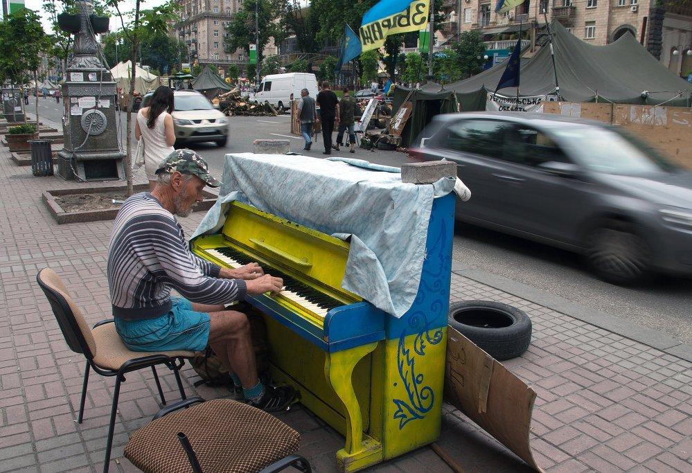 Мужчина играет на фортепиано напротив палаточного лагеря на улице Крещатик в Киеве