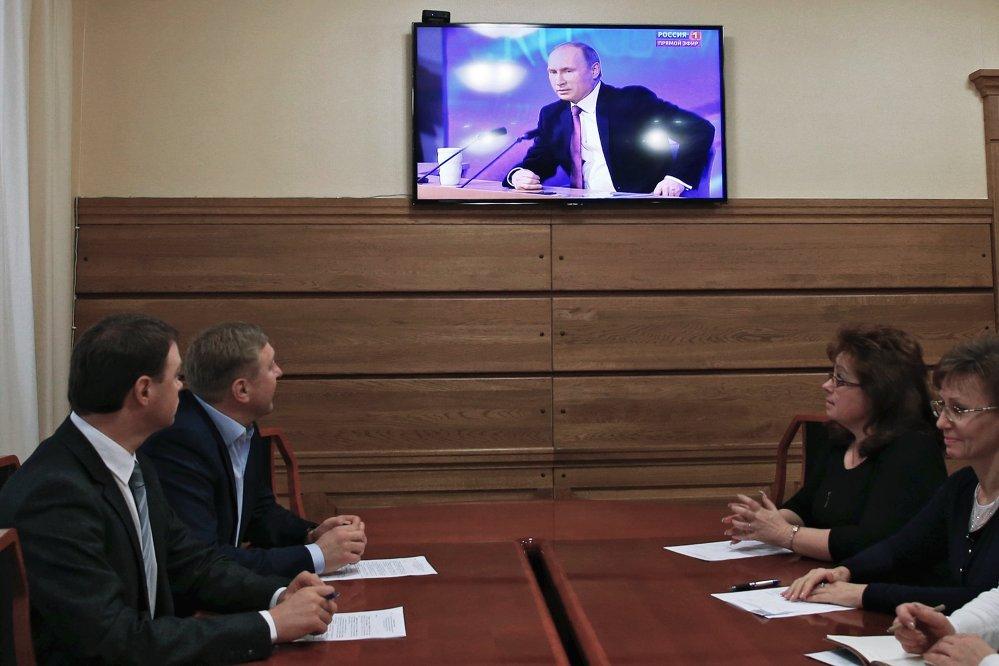 El alcalde de Kaliningrado, Alexandr Yaroshuk (segundo a la izquierda) sigue la transmisión televisiva de la gran rueda de prensa del presidente Vladímir Putin