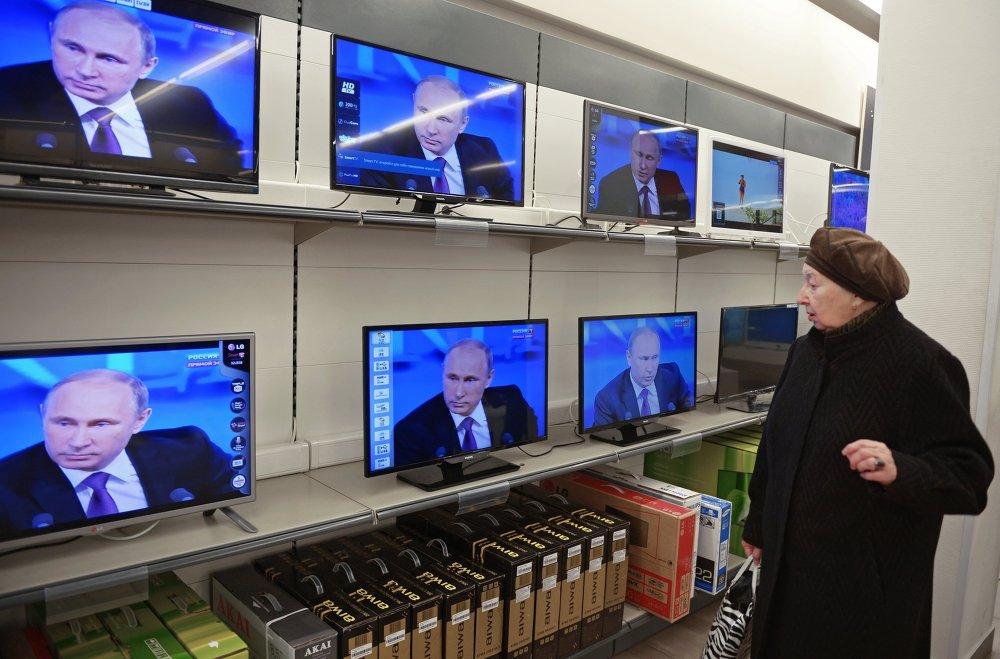 Una mujer viendo la transmisión de la gran rueda de prensa del presidente Vladímir Putin, en una tienda de equipos electrónicos de Moscú