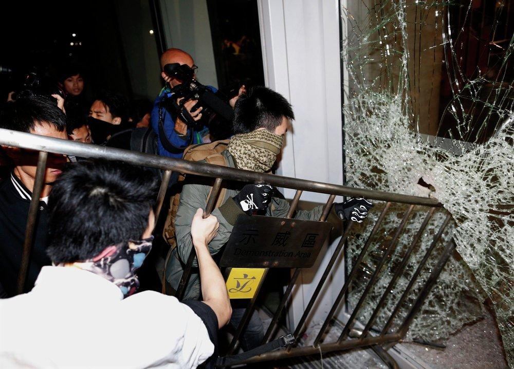 Протестующие пытаются выломать забором окно в здании Законодательного совета Гонконга