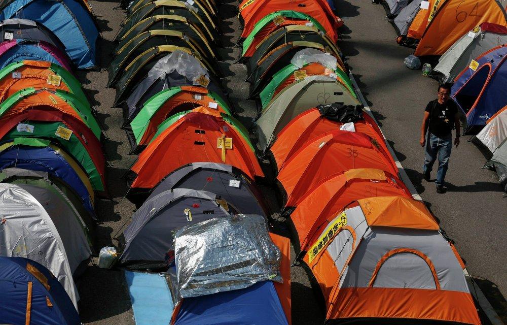 Протестующий идет между палатками центральном районе Гонконга